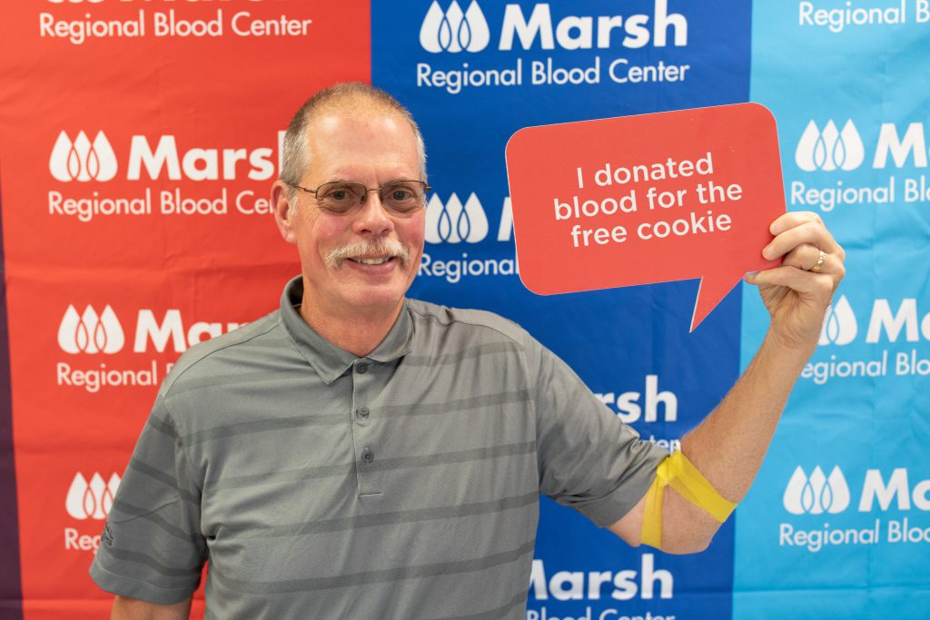 """Smiling man holds sign that says """"I donated blood for the free cookie"""""""
