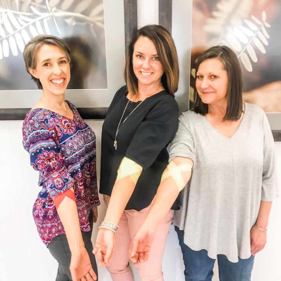 Three smiling women extend their arms to show that they gave blood