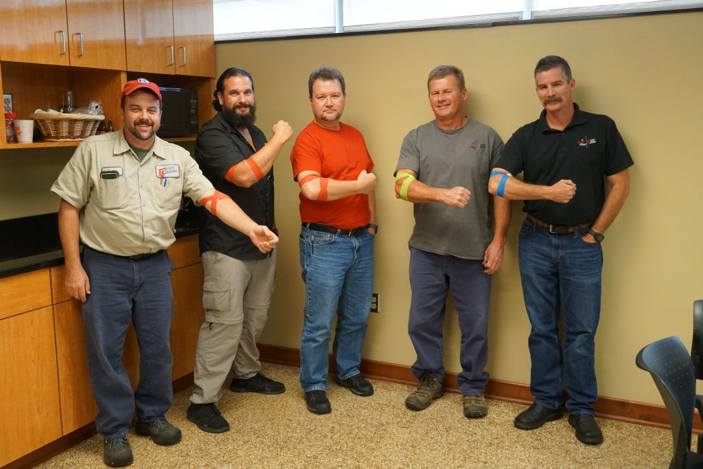 Five men flex their arms to show their bandages after giving blood