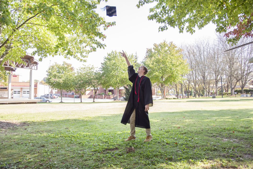 High school graduate tosses cap in the air and wears red cord from being a loyal blood donor