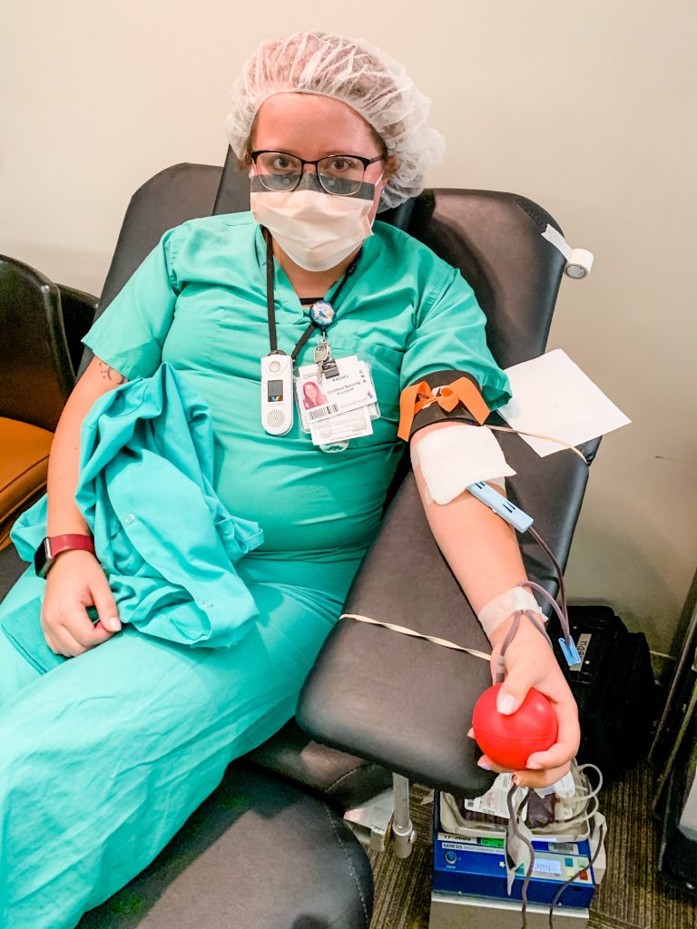 Heath care professional wearing scrubs, mask and hair net donates blood